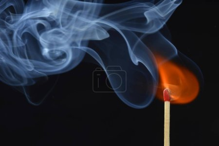 Lit matchstick with flame and smoke at black background