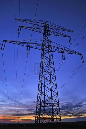 Electricity pylon against blue evening sky