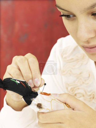 cropped image of woman sticking needles into voodoo doll