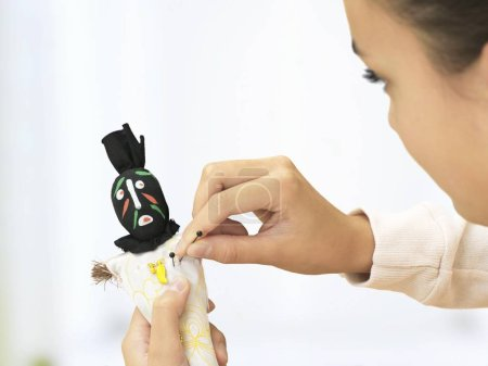 Woman sticking needles into voodoo doll