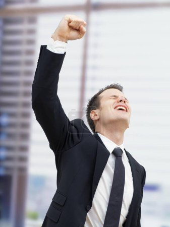 Businessman in office cheering with clenched fist, hand raised up