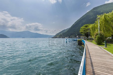 lake with mountains and islands in Italy, wooden walk path on coast