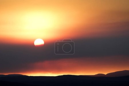 Orange sunset in sky with smoke cloud...