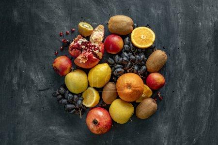 Photo pour Plat déposer fruits frais sélection disposition sur une surface grunge tels que raisins, kiwi, orange, fruits tropicaux exotiques - image libre de droit