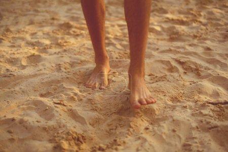 Photo pour Pieds nus masculins marchent sur la plage de sable, concept de pratique de yoga sain - image libre de droit
