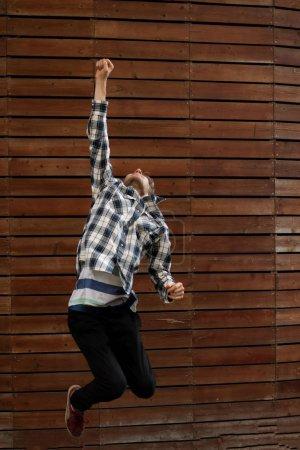 Photo pour Un jeune homme saute haut, signe de victoire ou de réussite - image libre de droit