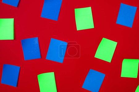 Photo pour Vue de dessus de quelques autocollants en papier couleur sur le fond du mur, idée abstraite - image libre de droit