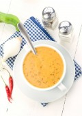 overhead shoot of spicy vegetable soup with chili, on white wooden board