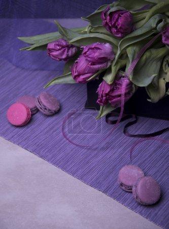 Photo pour Gros plan de tulipes violettes dans un panier en bois et macarons sur fond de couleur - image libre de droit
