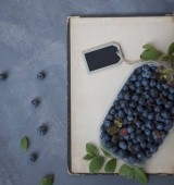 blueberries in basket and tag on grey background