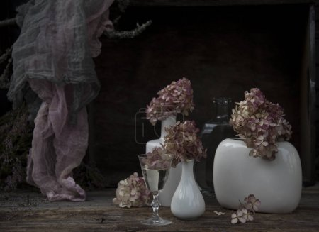 Photo for Still life with white vases with hydrangeas on dark background - Royalty Free Image