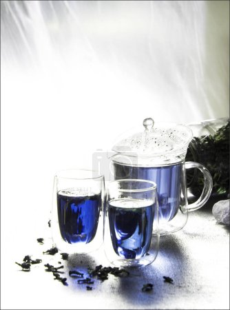 Photo for Glass teapot and cups with blue floral and herbal tea - Royalty Free Image