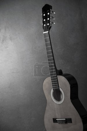 Photo for Monochrome photo of acoustic guitar on grey background - Royalty Free Image