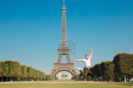 Photo pour Tour Eiffel. Le type en t-shirt blanc, baskets et jeans verts a sauté dans l'air, les mains dans la main. Jour d'automne chaud et ensoleillé . - image libre de droit