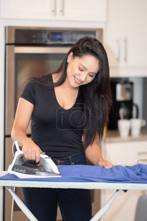 Photo for Woman ironing a set of clothes in her home - Royalty Free Image