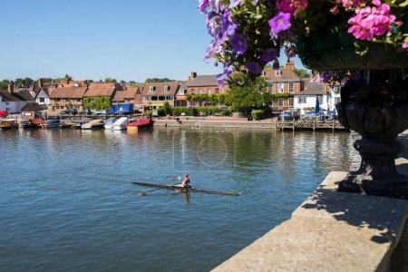 Skyline Of Henley On Thames In Oxfordshire UK With Rower On River Thames In Foreground