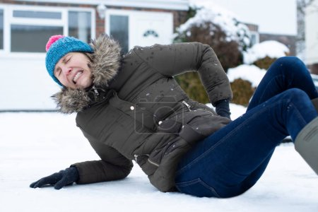 Woman In Pain Falling Over In Snowy On Slippery St...