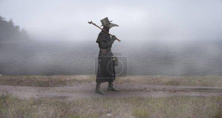 Photo pour L'époque médiévale. Le médecin de la peste marche le long de la route près du lac brumeux - image libre de droit