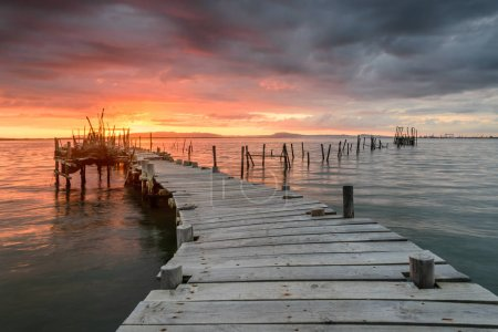 Photo for Sunset landscape of artisanal fishing boats in the old wooden pier. Carrasqueira is a tourist destination for visitors to the coast of Alentejo near Lisbon. - Royalty Free Image