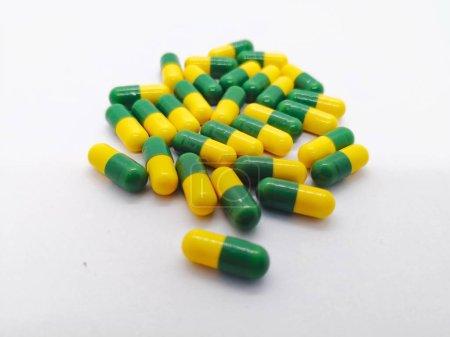 Photo pour Concept de médicament. Beaucoup de capsules jaune-vert de Tramadol 50 mg. isolées sur fond blanc, narcotiques comme analgésique, utilisées pour traiter la douleur modérée à sévère. Mise au point sélective et espace de copie . - image libre de droit