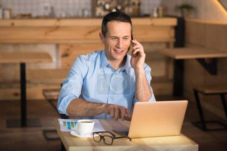 Photo pour Homme d'affaires souriant travaillant sur ordinateur portable dans un café tout en parlant sur smartphone - image libre de droit