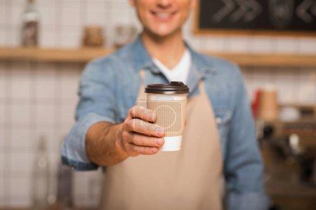 recortado tiro de camarero sosteniendo café para ir en taza de papel con fondo borroso
