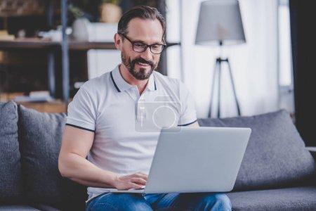 Photo pour Portrait d'un homme barbu portant des lunettes travaillant sur un ordinateur portable à la maison - image libre de droit