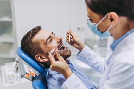 Photo pour Portrait de dentiste en masque médical vérifiant les dents du patient avec miroir dans une clinique dentaire - image libre de droit