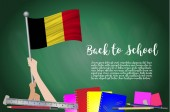 Vector flag of Belgium on Black chalkboard background Education Background with Hands Holding Up of Belgium flag Back to school with pencils books school items learning and childhood concept