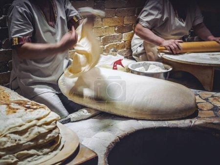 cropped shot of men preparing lavash on market at Armenia