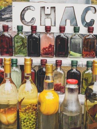 Photo pour Boisson alcoolisée géorgienne traditionnelle chacha en bouteilles avec différents fruits et herbes au marché - image libre de droit
