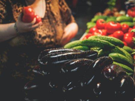 Photo pour Image recadrée d'une femme tenant des tomates sur le marché géorgien avec des aubergines au premier plan - image libre de droit