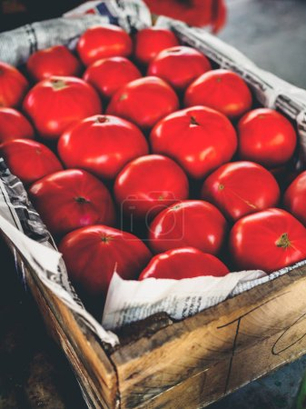 ripe red tomatoes in wooden box at georgian market