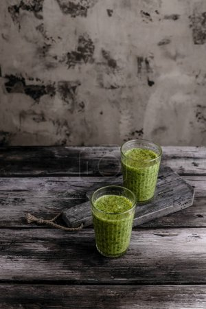 Delicious green smoothie in glasses on rustic wooden table