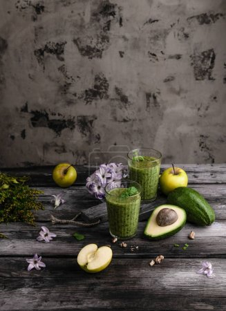 Green fruit smoothie in glasses on wooden background with flowers