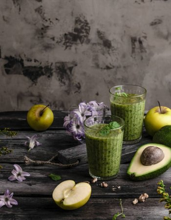 Delicious detox smoothie on rustic wooden board with fruits and flowers