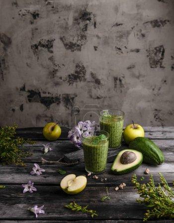 Photo pour Smoothie fruits biologiques sur fond en bois avec fruits et fleurs - image libre de droit