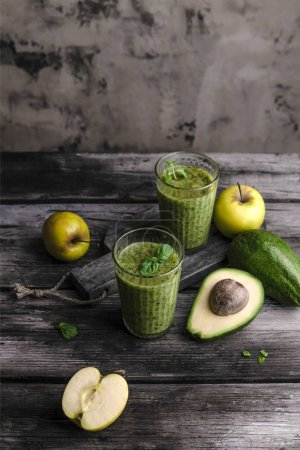 Fresh healthy smoothie with apples and avocado on rustic table