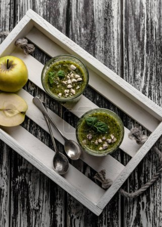 Delicious green smoothie in glasses on rustic wooden board