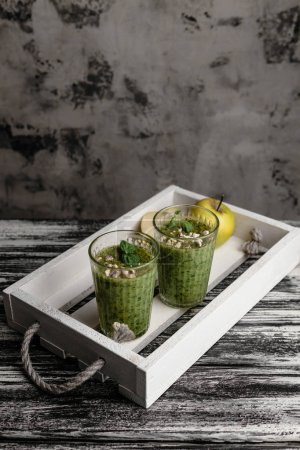 Fresh healthy green smoothie in glasses on rustic tray