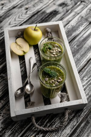Delicious detox smoothie in glasses on rustic wooden tray