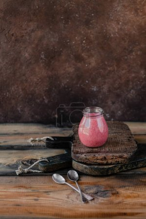 Organic berry smoothie in jar on wooden background