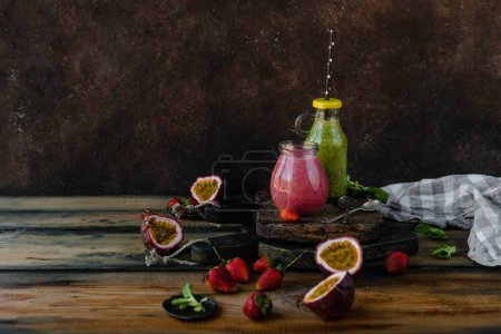 Fresh healthy smoothies on rustic table with berries and passion fruit
