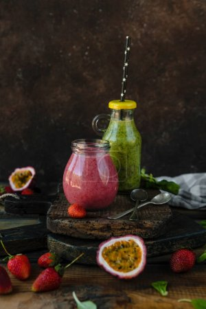 Organic fruit smoothie on wooden background with herbs and berries