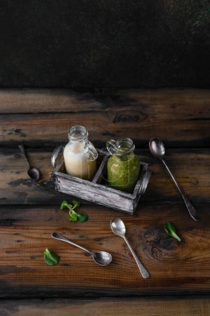 Fresh healthy green and white smoothies on rustic table