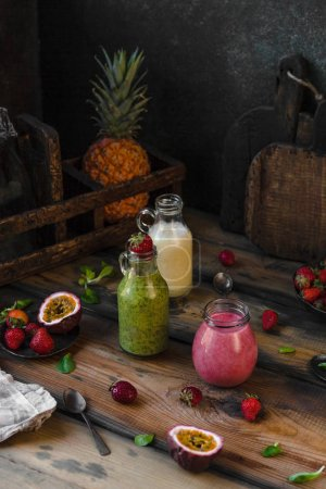 Delicious detox smoothies in bottles on rustic wooden board