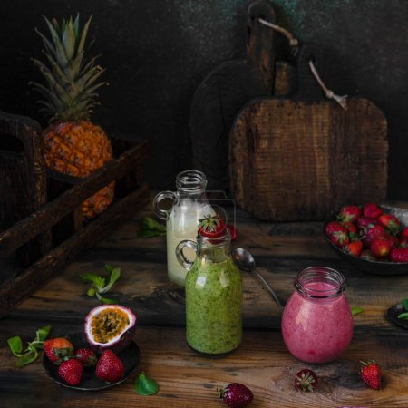 Organic fruit smoothies on wooden background with pineapple and berries