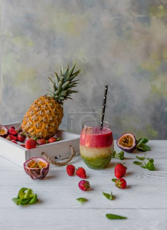 Organic layered fruit smoothie on wooden background with exotic fruits