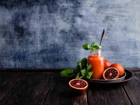 Organic orange juice with basil leaves on wooden background