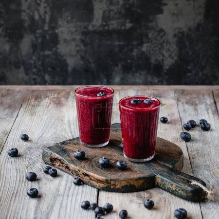 Photo for Fresh healthy berry smoothie in glasses on rustic table - Royalty Free Image